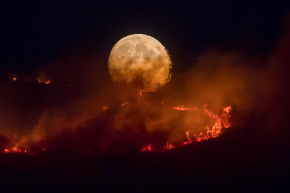 The full moon rises behind burning moorland in a spectacular image captured on Tuesday
