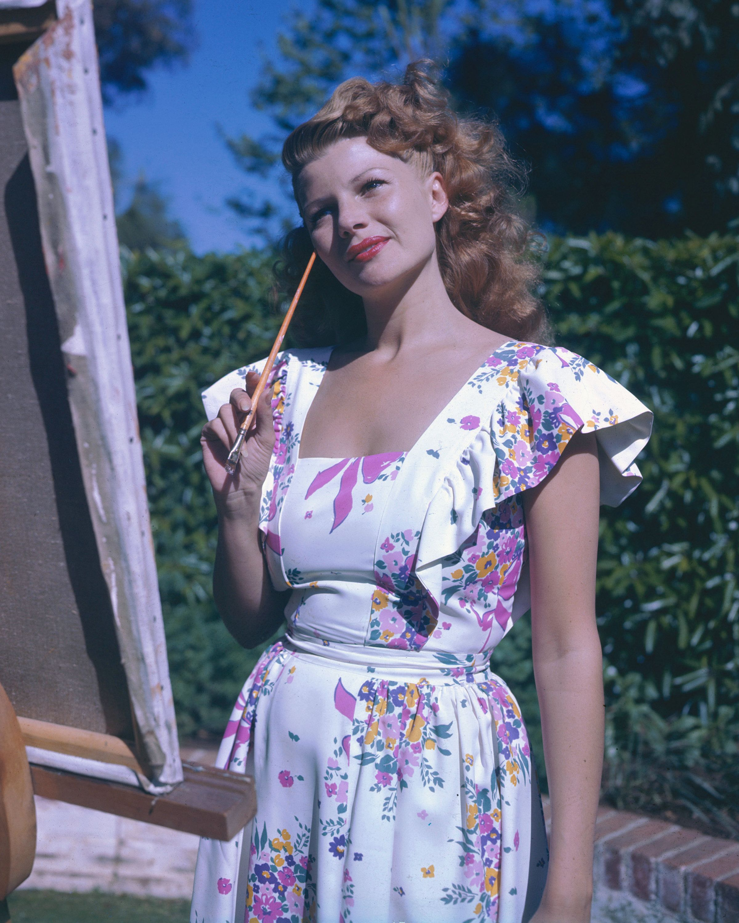 Rita Hayworth (1918-1987), US actress and dancer, wearing a sleeveless white floral print dress, posing with a paintbrush beside an easel, circa 1945. (Photo by Silver Screen Collection/Getty Images)