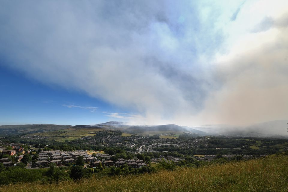 Plumes of smoke rise above Stalybridge as the wildfire enters afourth