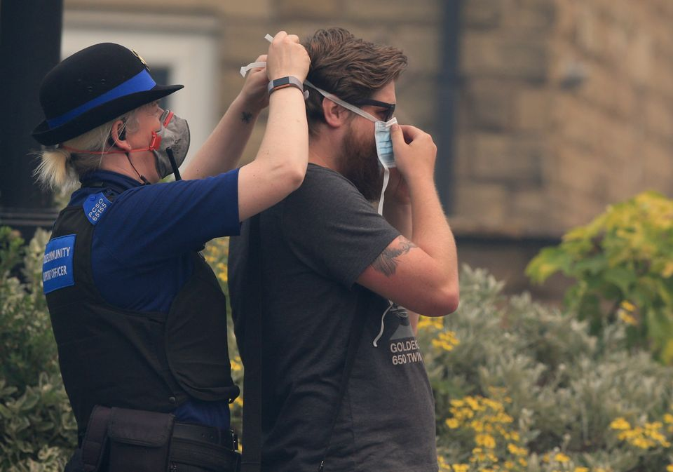 A PCSO assists a member of the public with face mask to protect gainst the smoke on Calico Crescent,...