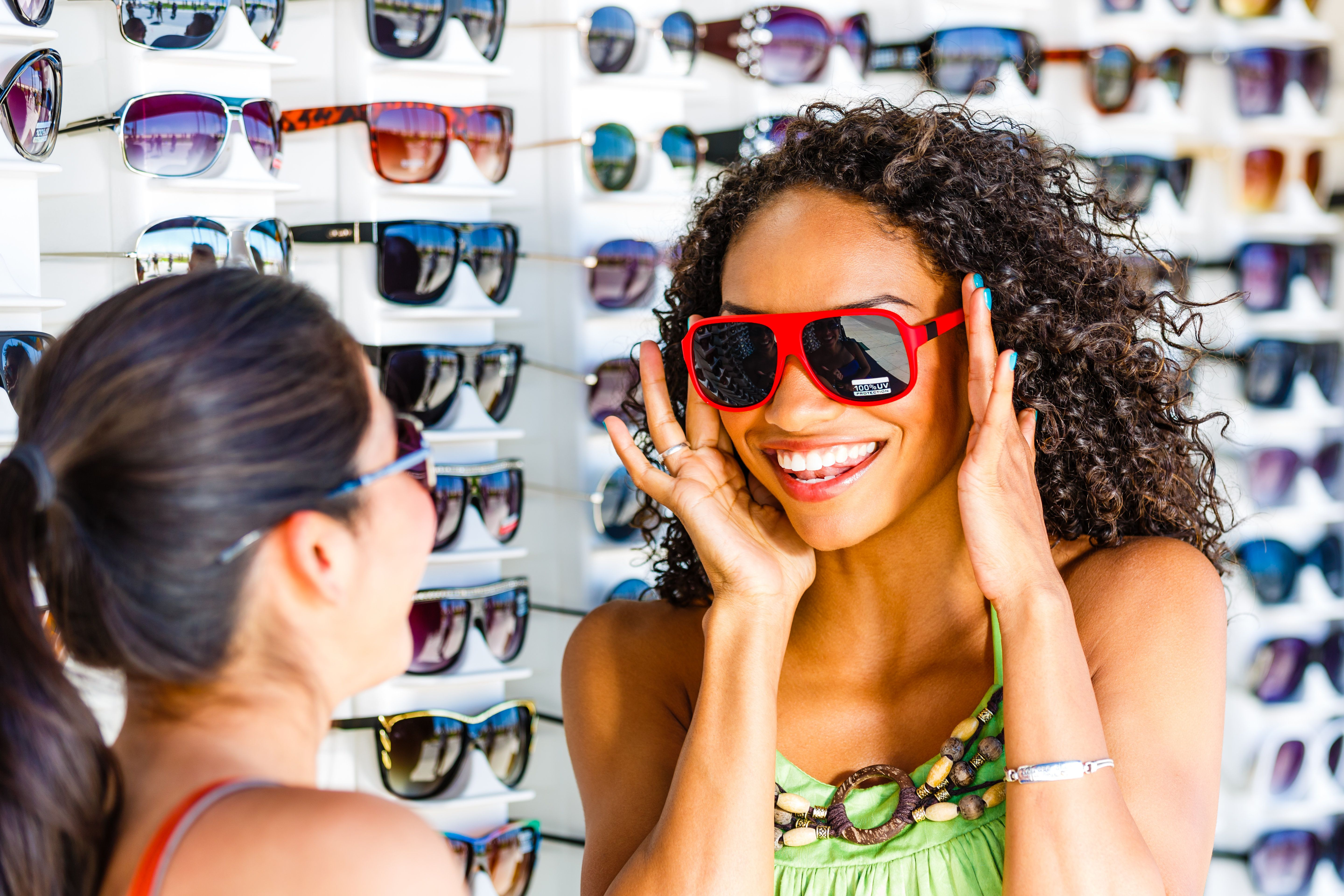 Young women having fun buying sunglasses at Venice beach, LA, USA.