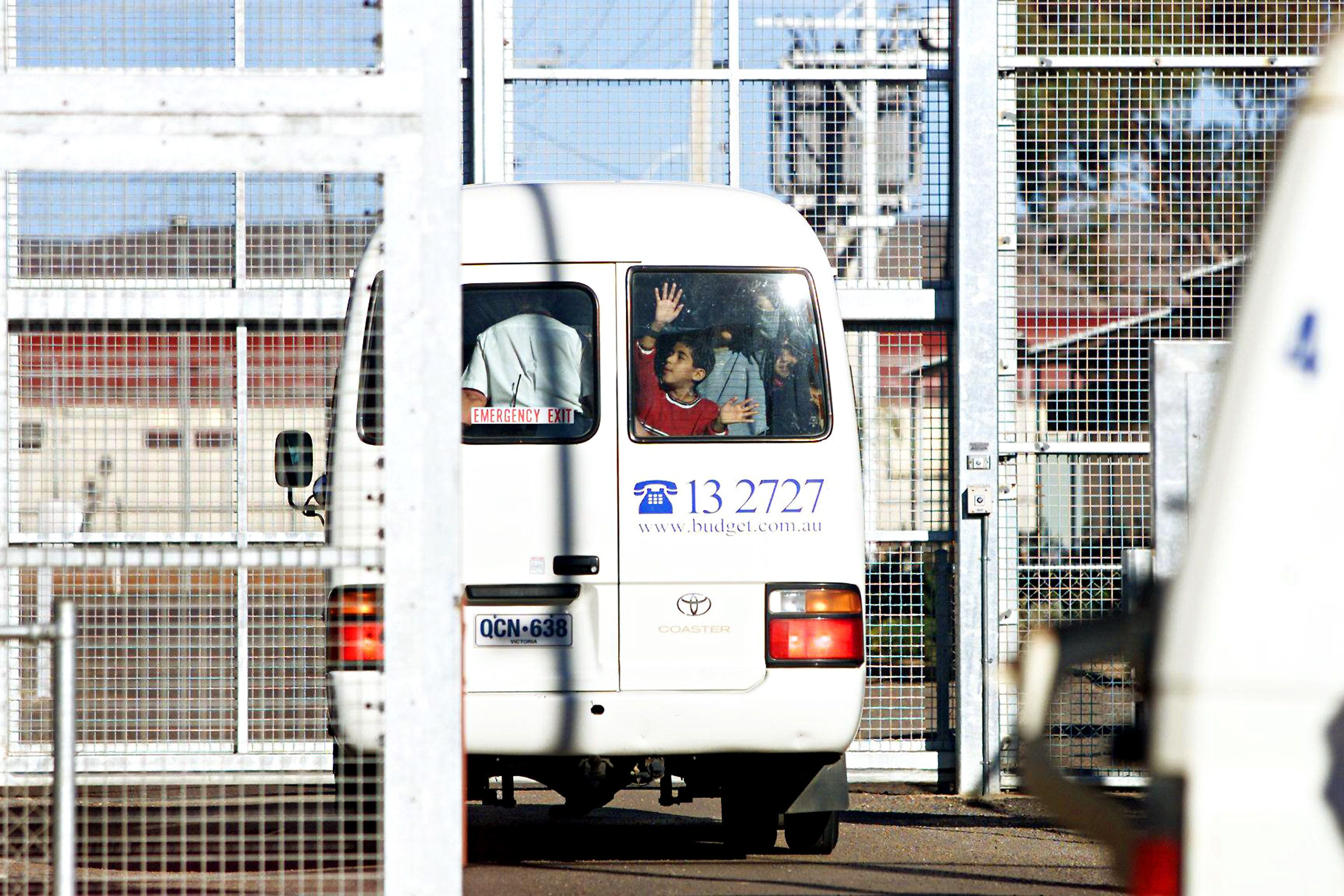 (AUSTRALIA OUT) The Big Picture. After school, a bus carries asylum-seeker children back behind the wire of the Baxter detention centre in 2003. Children sewed their mouths shut, drank shampoo, cut themselves with razors and threatened suicide in protest against their detention. The Federal Government decided to release children from detention in 2005 after lobbying from its back bench, 1 August 2003. AFR Picture by BRYAN CHARLTON (Photo by Fairfax Media via Getty Images)