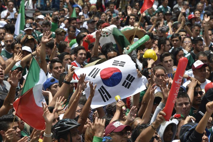 A football fan holds a flag of South Korea as thousands watch the World Cup match between Mexico and Sweden on a screen in Me