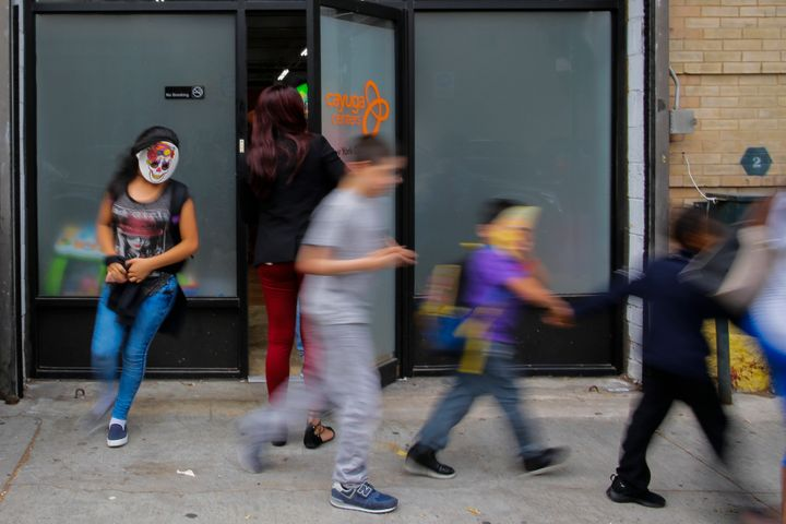 Children with masks exit the Cayuga Centers branch on June 22 in Harlem, New York. The youngest migrant at Cayuga is 9 m