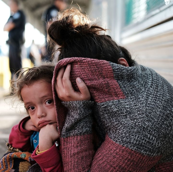 A Honduran child and her mother, fleeing poverty and violence in their home country, wait along the border bridge after being