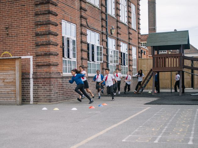 Schoolchildren run around their playground as part of a 'Marathon Kids' session.