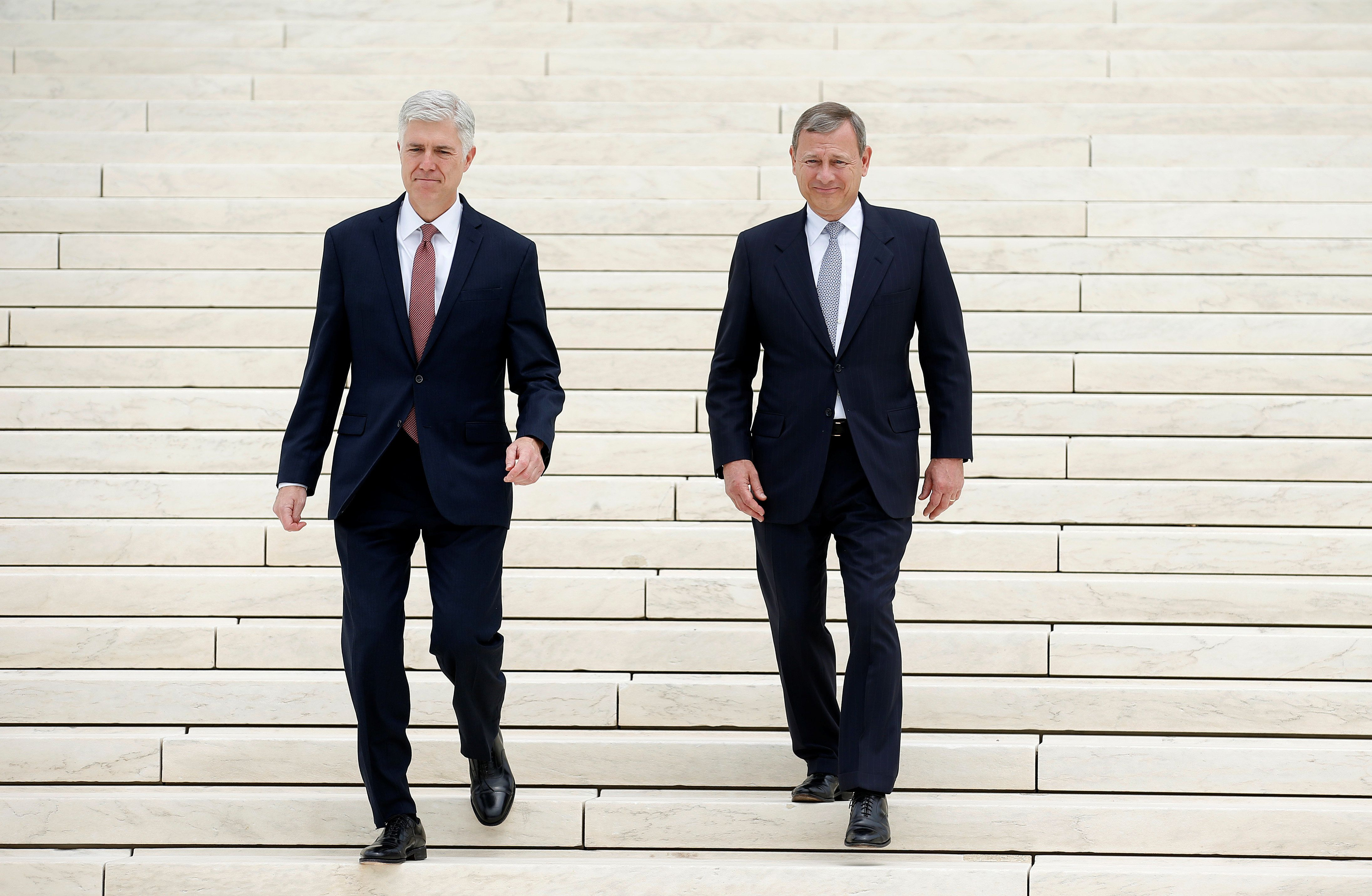 Chief Justice of the United States John Roberts (R) walks with associate Justice Neil Gorsuch during his investiture ceremony at the Supreme Court in Washington, U.S., June 15, 2017.   REUTERS/Joshua Roberts