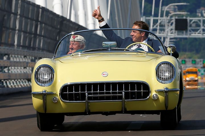 "Andrew Cuomo drives a 1955 Chevrolet Corvette with World War II veteran Armando ""Chick"" Gallela, during a dedication ceremony"