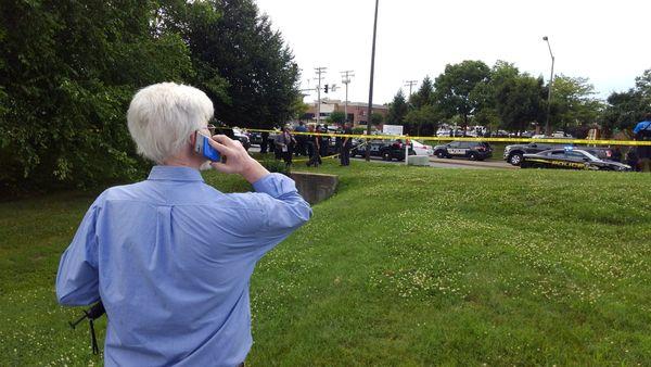 E.B Furgurson talks on the phone outside the scene.