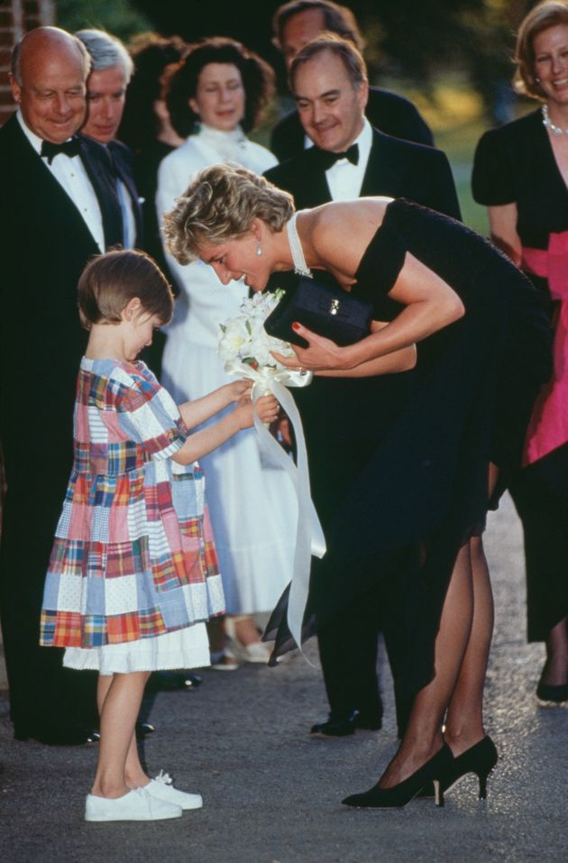 Diana receives a bouquet from a young girl as she arrives for the gala event at the Serpentine