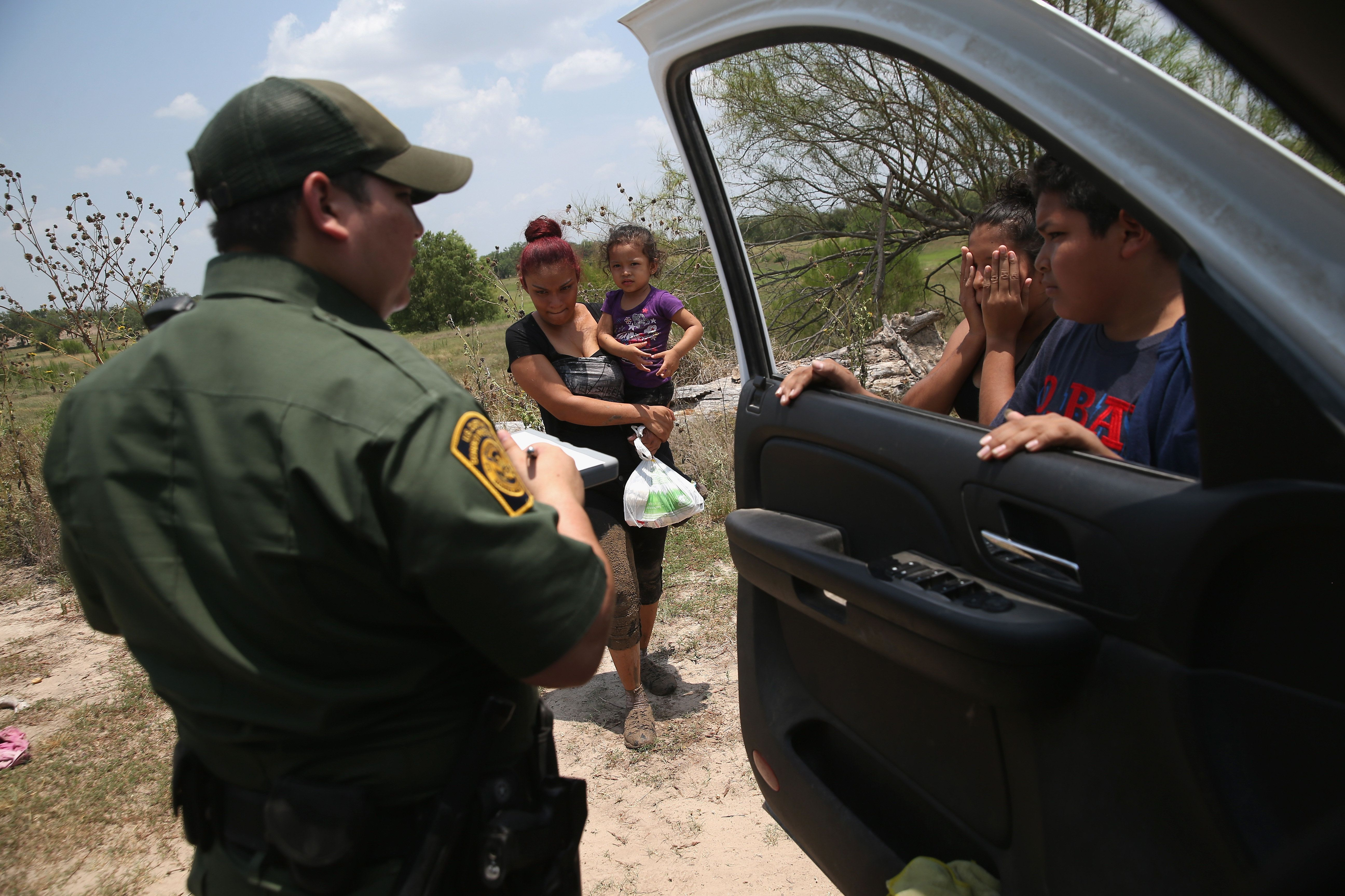 MISSION, TX - JULY 24:  A U.S. Border Patrol agent takes biograpical information from unaccompanied minors from El Salvador after they crossed the Rio Grande illegally into the United States on July 24, 2014 in Mission, Texas. Tens of thousands of immigrant families and unaccompanied minors have crossed illegally into the United States this year and presented themselves to federal agents, causing a humanitarian crisis on the U.S.-Mexico border.  (Photo by John Moore/Getty Images)