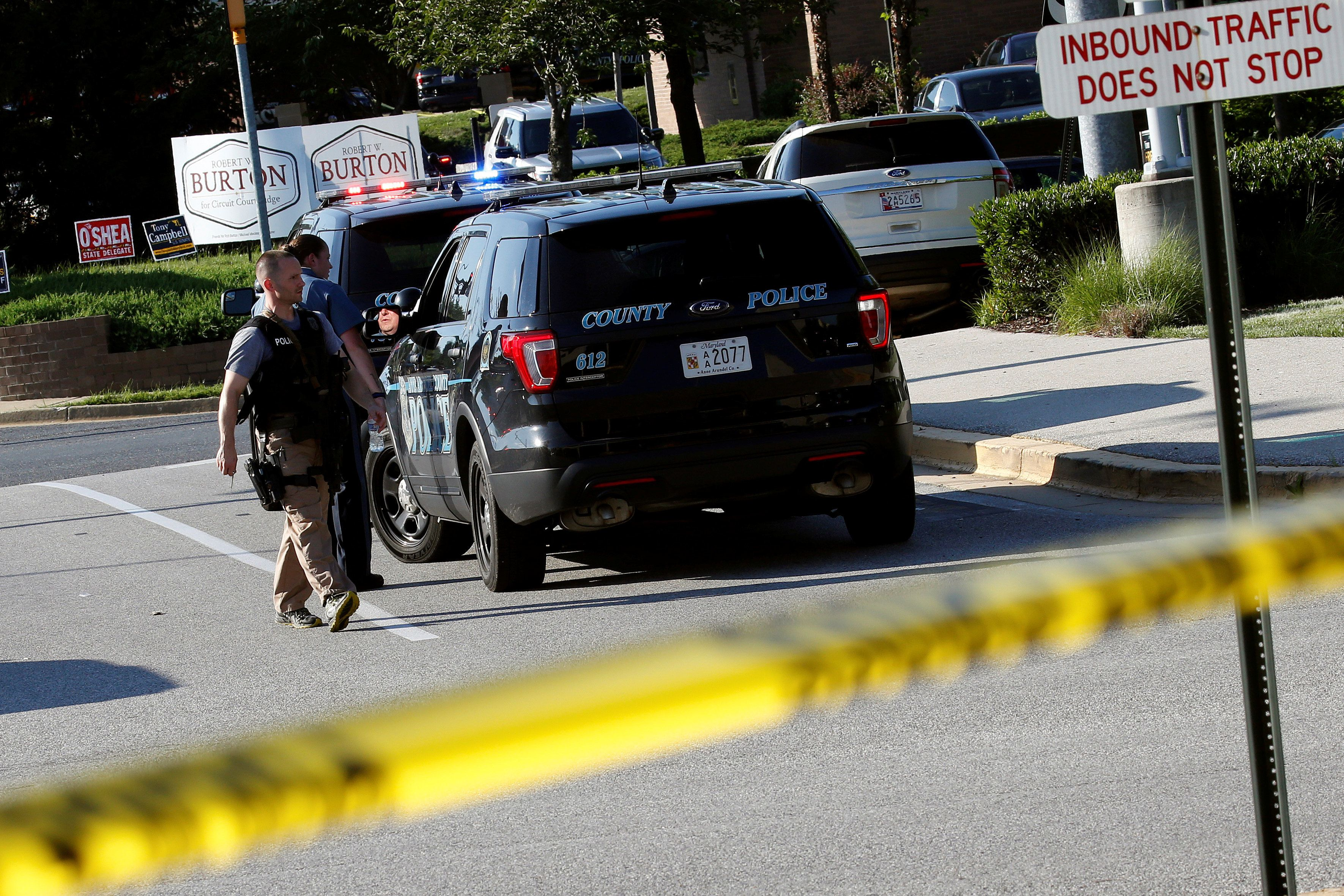 Police walk past a vehicle near a shooting scene after a gunman opened fire at the Capital Gazette newspaper in Annapolis, Maryland, U.S. June 28, 2018. REUTERS/Joshua Roberts