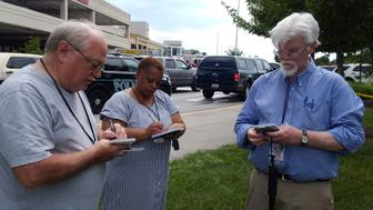 Journalist E.B Furgurson (R) takes notes with two other people as police officers respond to an active shooter inside a city building at the Capital Gazette newspaper office in Annapolis, Maryland, U.S., June 28, 2018.   REUTERS/Greg Savoy