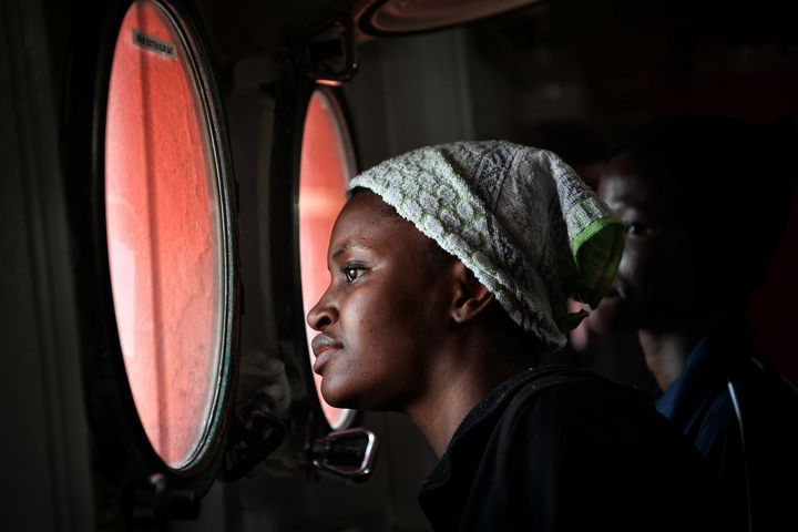 A migrant peers out from the porthole of the MV Aquarius upon its arrival at the Sicilian port of Messina, on May 14, 2018.&n