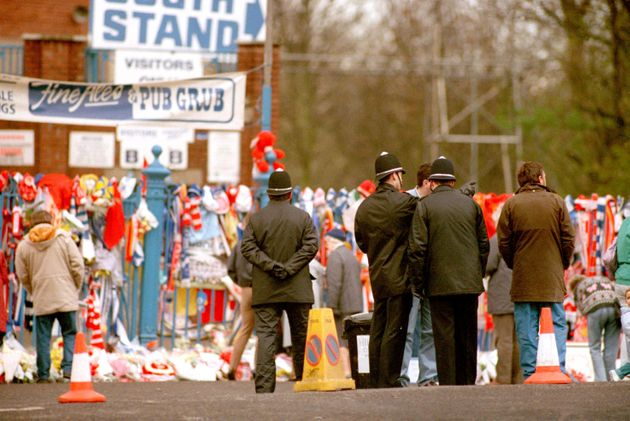 Policemen stand outside the Leppings Lane end of the Hillsborough ground as tributes accumulate following...