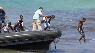 Migrants leave a boat at the coast of Tajoura, east of Tripoli, Libya June 20, 2018. REUTERS/Hani Amara