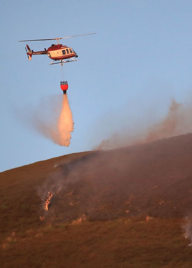 A helicopter drops wateron the fire which could continue to burn for