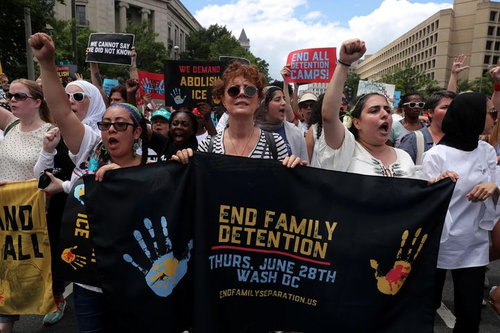 Sarandon holds a banner as immigration activists rally on June 28, 2018.