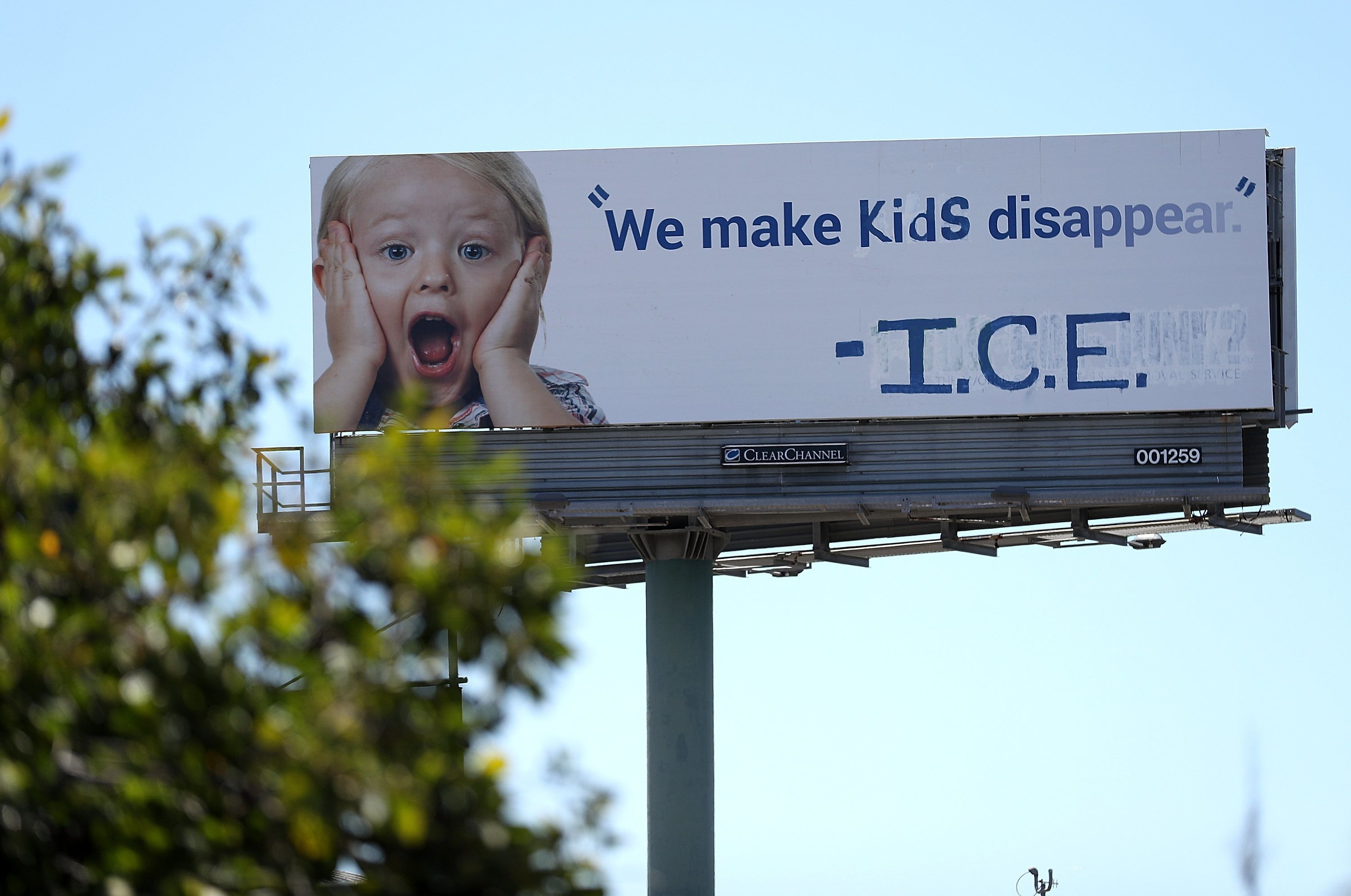 A vandalized billboard in Emeryville, California, shows a message protesting ICE's forcible separation of children