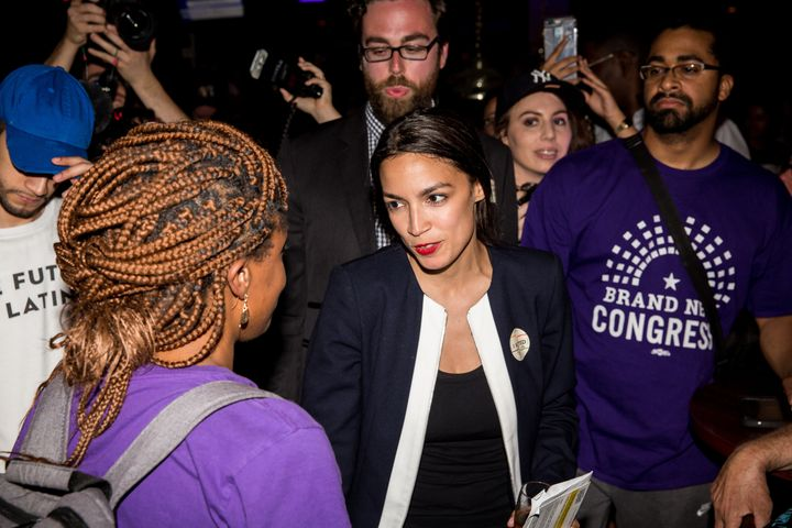 Progressive challenger Alexandria Ocasio-Cortez, center, celebrates with supporters at a victory party in the Bronx in New Yo