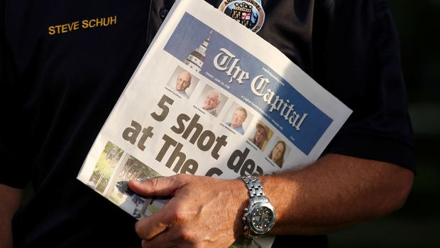Steve Schuh, the County Executive of Anne Arundel County, Maryland, holds a copy of the Capital Gazette as he is interviewed the day after a gunman killed five people and injured several others at the newspaper's offices, in Annapolis, Maryland, U.S., June 29, 2018. REUTERS/Joshua Roberts