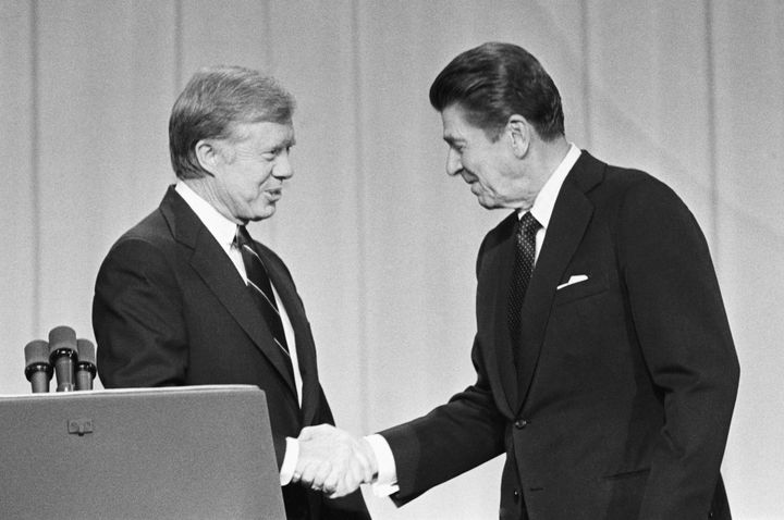 President Jimmy Carter and his Republican challenger, Ronald Reagan, shake hands before their presidential debate in 198