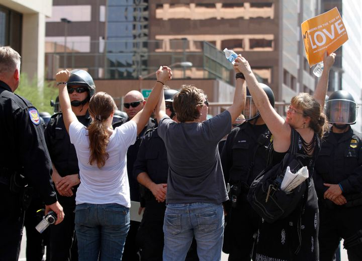 Demonstrators sand in front of riot police with their arms in the air during a protest against Arizona's controversial Senate