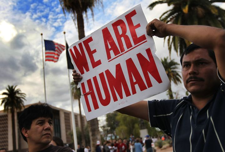 Demonstrators protest Arizona's new immigration law outside the Arizona state capitol building on April 23, 2010 in Phoenix,