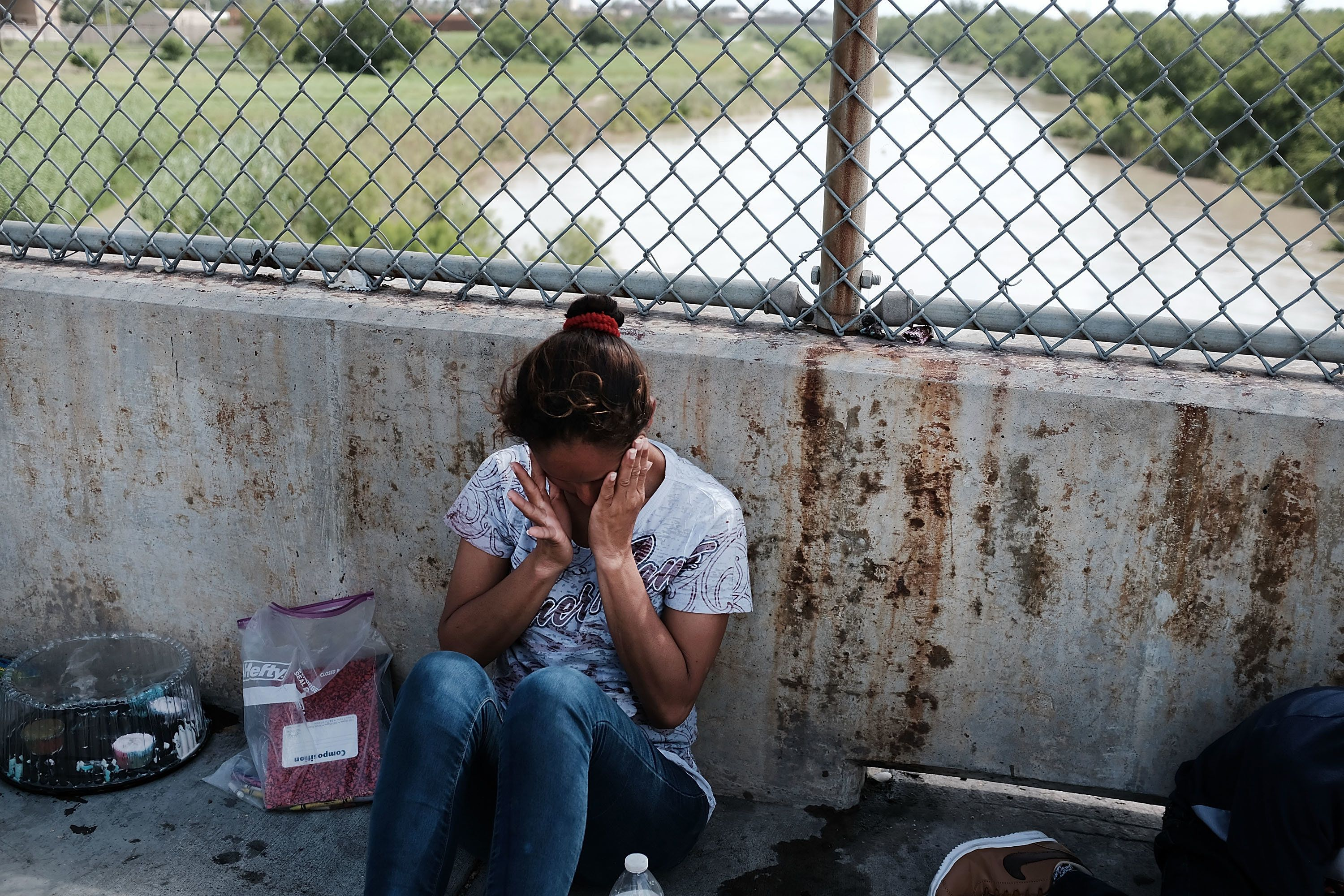 A Honduran woman, fleeing poverty and violence in her home country, waits along the border bridge after...