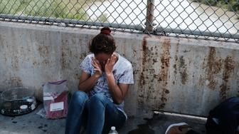 BROWNSVILLE, TX - JUNE 25:  A Honduran woman, fleeing poverty and violence in her home country, waits along the border bridge after being denied entry into the U.S. from Mexico on June 25, 2018 in Brownsville, Texas. Immigration has once again been put in the spotlight as Democrats and Republicans spar over the detention of children and families seeking asylum at the border. Before President Donald Trump signed an executive order last week that halts the practice of separating families who are seeking asylum, more than 2,300 immigrant children had been separated from their parents in the zero-tolerance policy for border crossers.  (Photo by Spencer Platt/Getty Images)