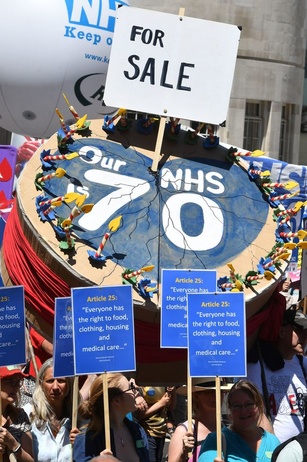 A giant NHS birthday cake with a 'for sale' sign in it was one of the hundreds of banners and placards at the rally.