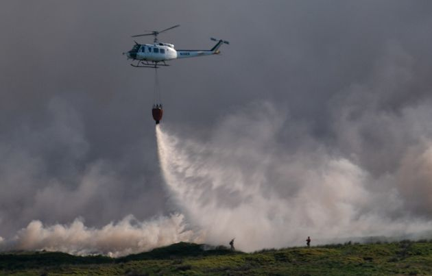 A helicopter drops water on the grass fire enveloping Winter Hill near Bolton on June 30, 2018 in Bolton,