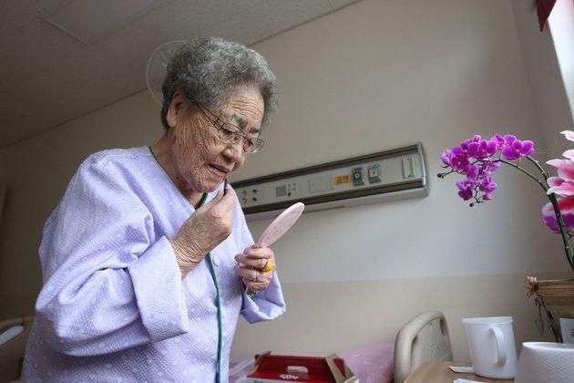 김복득 할머니가 2014년 7월 22일 경남도립 통영노인전문병원에서 매주 열리는 자원봉사자들의 노래자랑을 보러 가기 위해 립스틱 바르며 단장하고