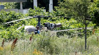 This picture taken on July 1, 2018 in Gonesse, north of Paris shows a forensic  policeman taking a picture of a French helicopter Alouette II abandoned by French armed robber Redoine Faid after his escape from prison in Reau. (Photo by GEOFFROY VAN DER HASSELT / AFP)        (Photo credit should read GEOFFROY VAN DER HASSELT/AFP/Getty Images)
