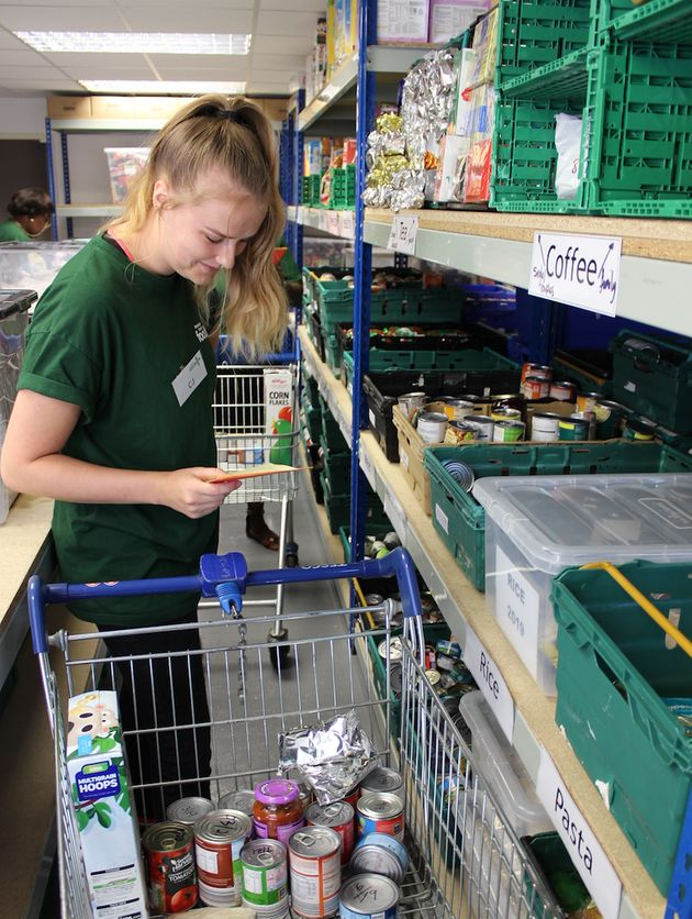 Birmingham Central Foodbank staff member CJ Glover collects items for a food package on a recent...