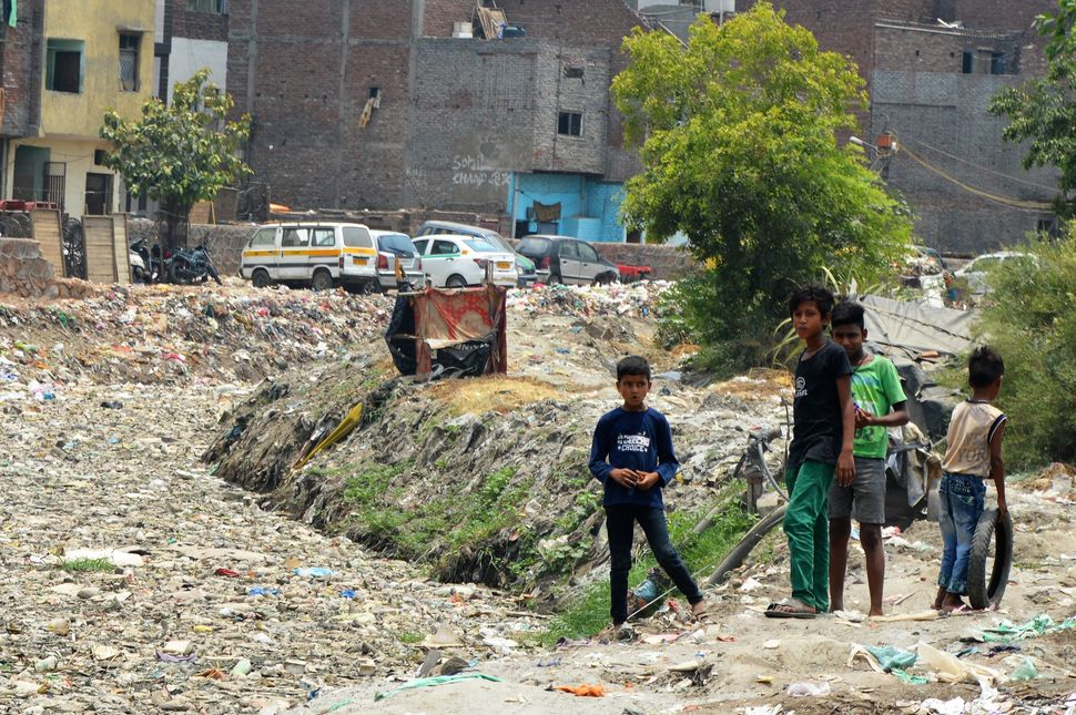 Nitesh Kumar (second from left) and friends play beside a canal covered in plastic waste near their homes in Geeta Colony, Ne