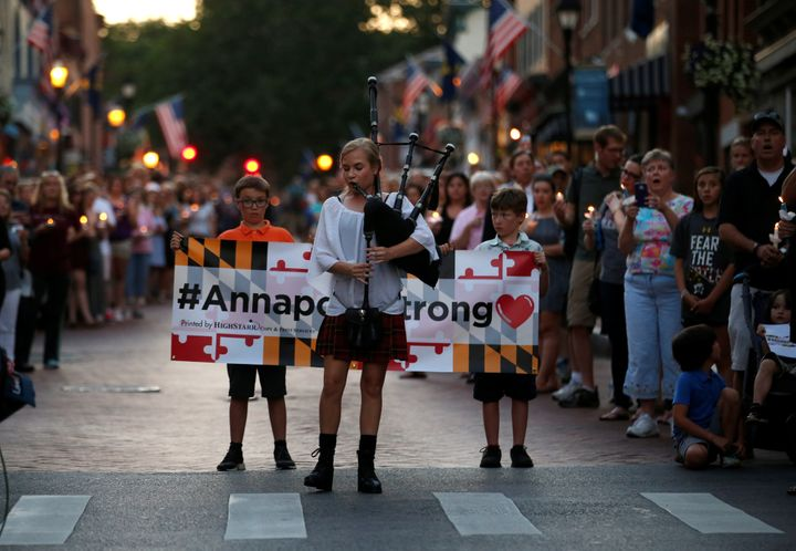 "People line the street as a woman plays ""Amazing Grace"" on a bagpipe during a June 29 candlelight vigil in downtown Annapolis"