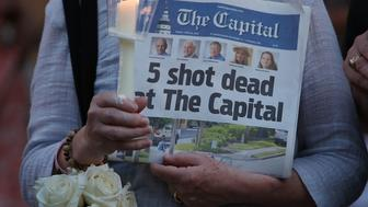 ANNAPOLIS, MD - JUNE 29: A women holds today's edition of the Capital Gazette newpaper during a candlelight vigil to honor the 5 people who were shot and killed yesterday, on June 29, 2018 in Annapolis, Maryland.  Jarrod Ramos of Laurel Md. Has been arrested and charged with killing 5 people at the daily newspaper.  (Photo by Mark Wilson/Getty Images)