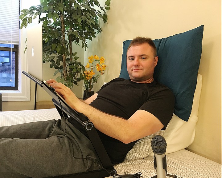 Rick Lunkenheimer lying at a 45-degree angle on a wedge pillow with extra pillow for neck support, configurable desk and micr