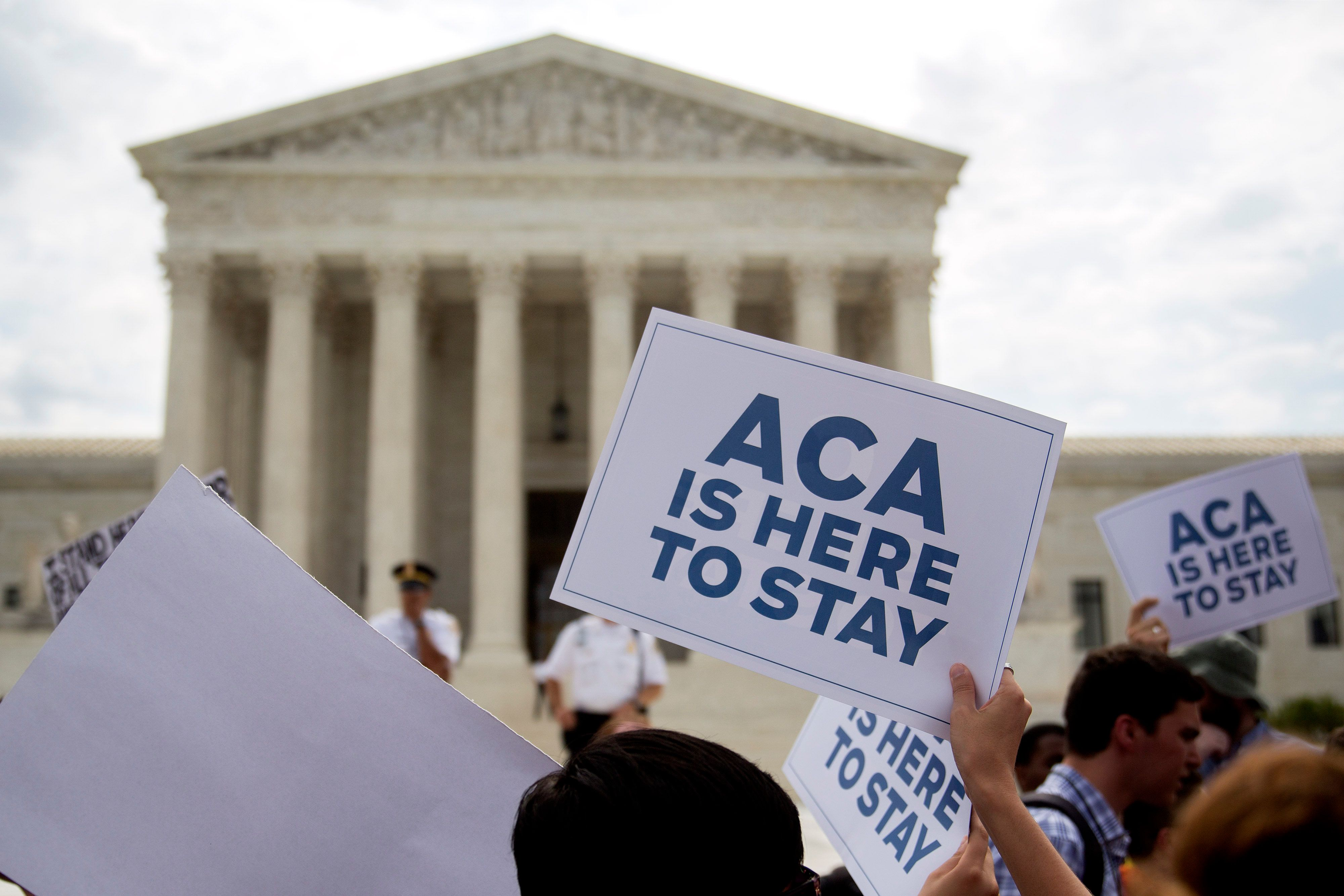 Demonstrators in support of U.S. President Barack Obama's health-care law, the Affordable Care Act (ACA), hold up 'ACA is Here to Stay' signs after the U.S. Supreme Court ruled 6-3 to save Obamacare tax subsidies outside the Supreme Court in Washington, D.C., U.S., on Thursday, June 25, 2015. The U.S. Supreme Court upheld the nationwide tax subsidies that are a core component of President Barack Obama's health-care law rejecting a challenge that had threatened to gut the measure and undercut his legacy. Photographer: Andrew Harrer/Bloomberg via Getty Images