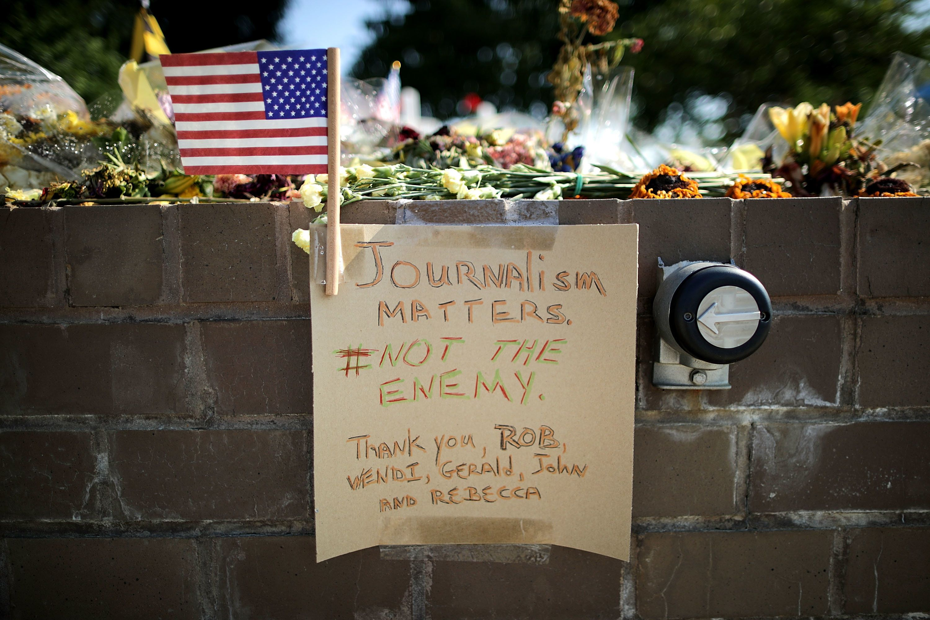 Flowers and hand-written notes were left by mourners at a makeshift memorial outside the Annapolis Capitol Gazette office for