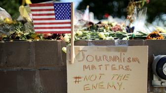 ANNAPOLIS, MD - JULY 02:  Flowers and hand-written notes and signs are placed at a makeshift memorial outside the Annapolis Capitol Gazette offices for the five employees killed by a gunman last week July 2, 2018 in Annapolis, Maryland. The five victims were Gerald Fischman, 61, an editorial editor; Rob Hiaasen, 59, an editor and columnist; John McNamara, 56, a sports reporter and editor; Wendi Winters, 65, a news reporter and columnist; and Rebecca Smith, 34, a sales assistant. Police arrested Jarrod Ramos, 38, in the paper's newsroom and he is being held without bond on five counts of murder.  (Photo by Chip Somodevilla/Getty Images)