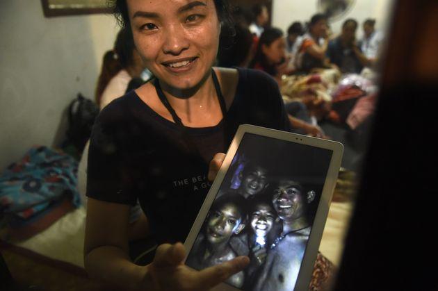 실종자의 가족이 사라진 12명의 아이들 중 4명의 사진을 들어보이고 있다. 2018년 7월