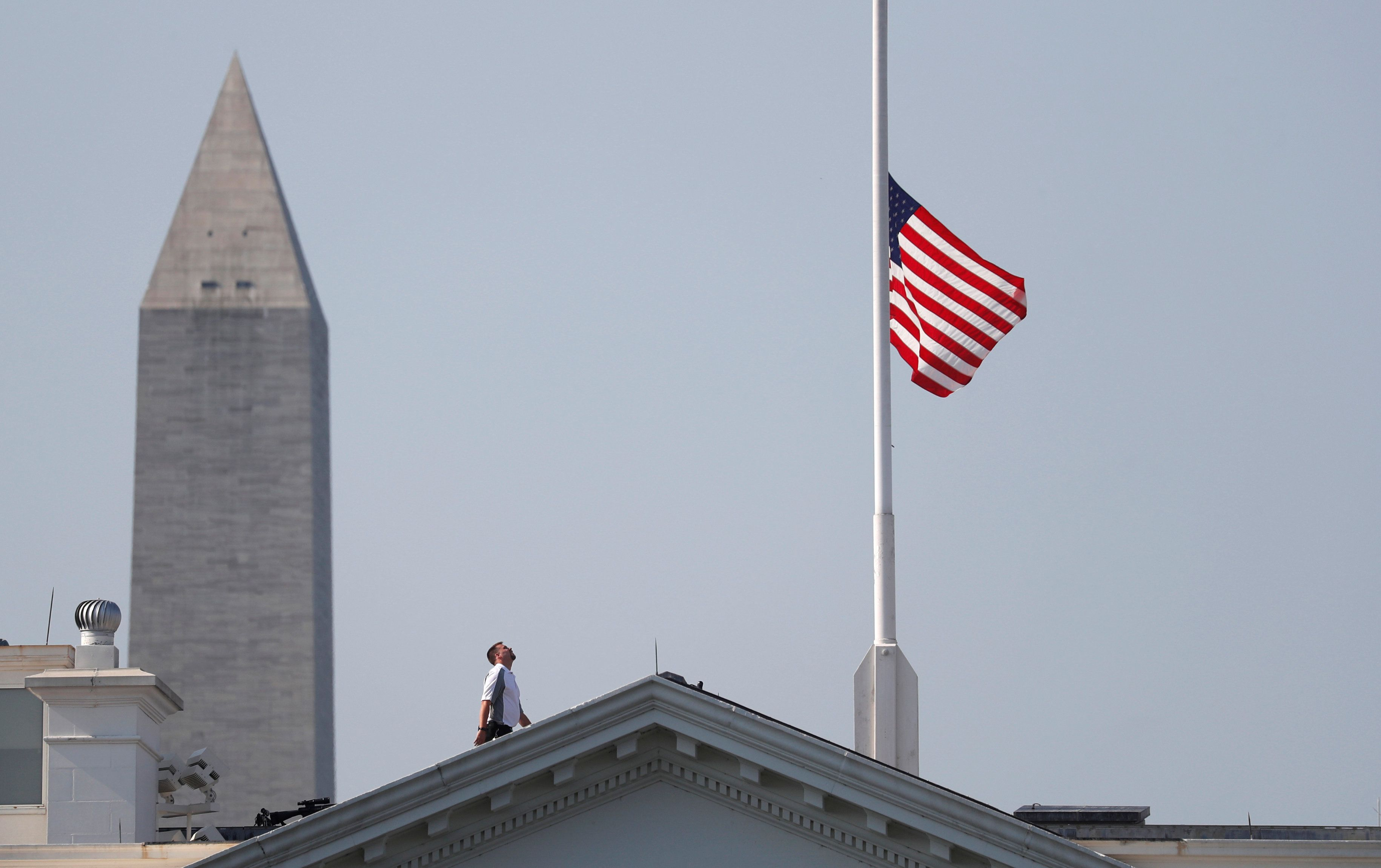 A worker looks up after lowering the flag over the White House in Washington to half-staff to honor victims of the shooting at the Capital Gazette Newspaper in Annapolis, Maryland, U.S., July 3, 2018.  REUTERS/Kevin Lamarque