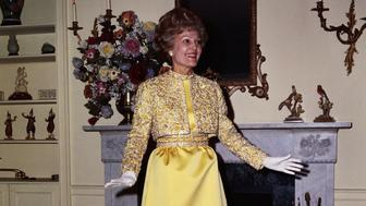 (Original Caption) In her apartment here, Mrs. Pat Nixon models the Harvey Berin gown that she will wear to the Inaugural Ball in Washington on January 20th. The mimosa yellow gown is of double-faced silk satin. The petite jacket and small waisted gown with its bell-shaped skirt is embroidered with Byzantine scrolls of gold and silver bouillon and embellished with hand set Swarovsky jewels in jonquil and crystal.