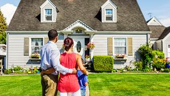 Photo of a young mixed-race family admiring a home - possibly their first home, or the home the hope to own.