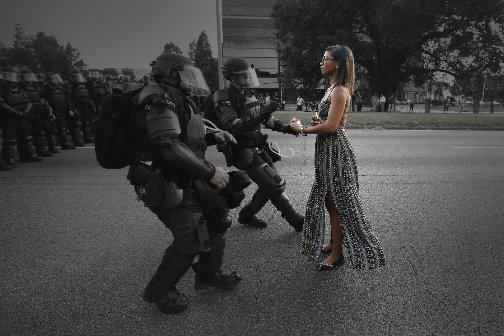 Lone activist Ieshia Evans stands her ground while offering her hands for arrest as she is charged by riot police during a protest against police brutality outside the Baton Rouge Police Department in Louisiana, USA, 9 July 2016. Evans, a 28-year-old Pennsylvania nurse and mother of one, traveled to Baton Rouge to protest against the shooting of Alton Sterling. Sterling was a 37-year-old black man and father of five, who was shot at close range by two white police officers. The shooting, captured on a multitude of cell phone videos, aggravated the unrest coursing through the United States in previous years over the use of excessive force by police, particularly against black men. REUTERS/Jonathan Bachman   TPX IMAGES OF THE DAY