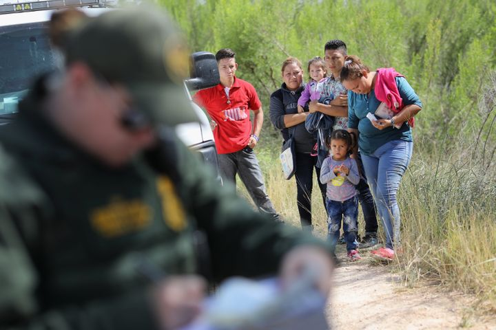 Central American asylum seekers wait as U.S. Border Patrol agents take groups of them into custody on June 12 near McAll