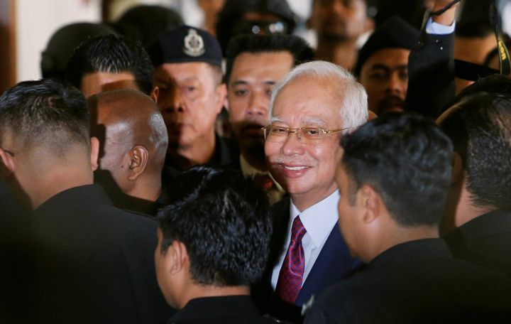 Former Malaysian prime minister Najib Razak reacts as he walks to a courtroom, after his arrival in court in Kuala Lumpur, Ma