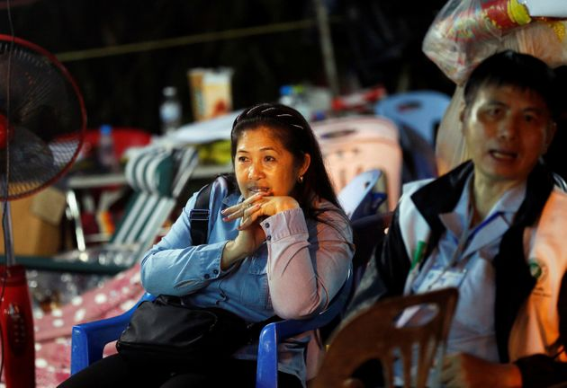 Family members of the trapped boys wait for news near the Tham Luang cave